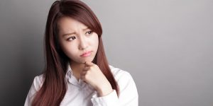 Thinking business woman and look copy space isolated on grey background with finger at face, asian beauty